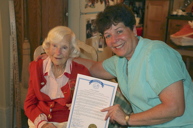 District 27A Rep. Peggy Bennett presents Dorothy Erlandson with a resolution during the party. - Photo courtesy of Dan Borland