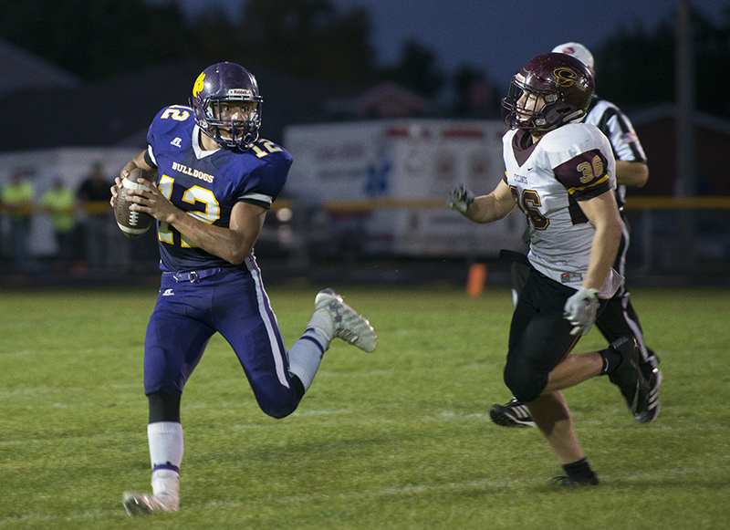 Lake Mills' Slade Sifuentes breaks out of the pocket to avoid getting sacked during Friday's game against Denver in Lake Mills. Sifuentes had to come in at quarterback after teammate Cael Boehmer came off the field with an injury during the second quarter. Colleen Harrison/Albert Lea Tribune