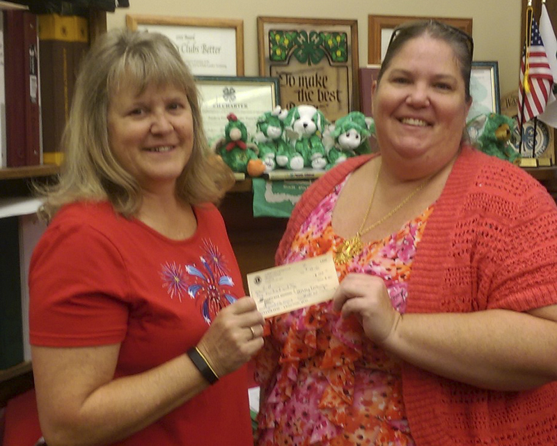 Wendy Weiss, left, of Freeborn County 4-H receives a $100 donation for the 4-H Playground from Albert Lea Lions President Tammy Krowiorz. - Provided