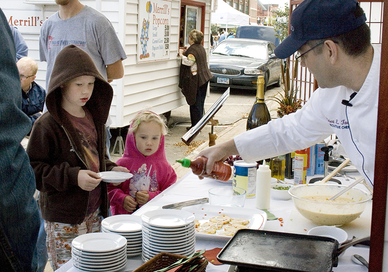 Bob Tewes, right, owner of Crescendo in downtown Albert Lea, adds some hot sauce to corn fritters he prepared during one of two cooking demonstrations at the fall festival in 2011. Tewes will again offer cooking presentations at the Autumn Blaze Festival. Tribune file photo