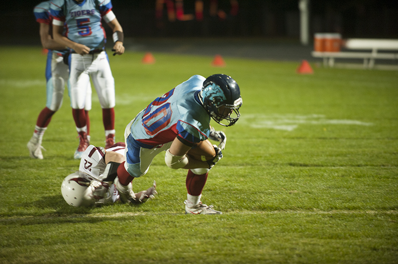 Albert Lea running back Dylan Lestrud falls forward after running through a tackle by Fairmont's Cody Freese in the first half Friday night. Lestrud led the Tigers in rushing yards with 69 on 12 carries.