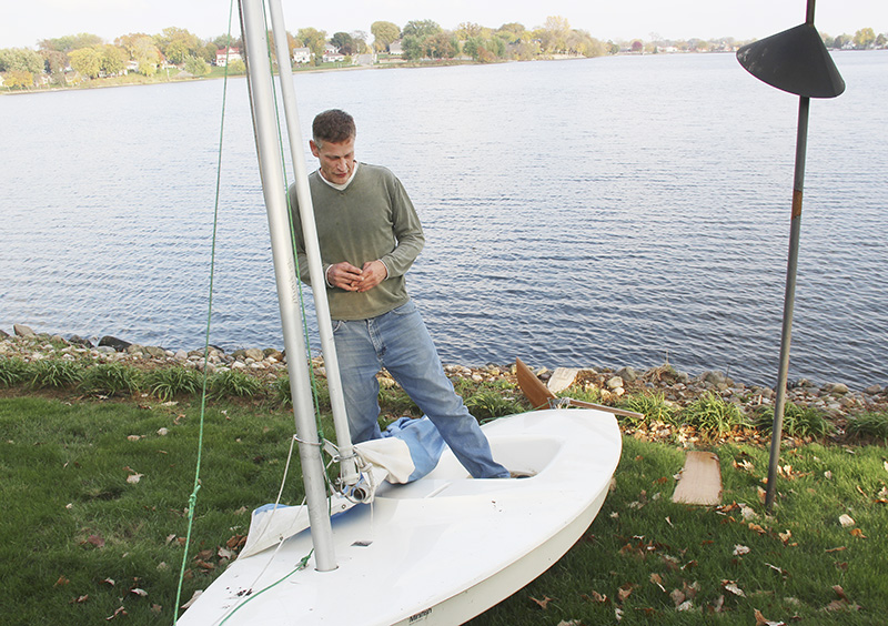 Albert Lean Kris Springborg looks at his sailboat in the backyard of a home on East Park Avenue where it was taken after he capsized Oct. 9. Sarah Stultz/Albert Lea Tribune