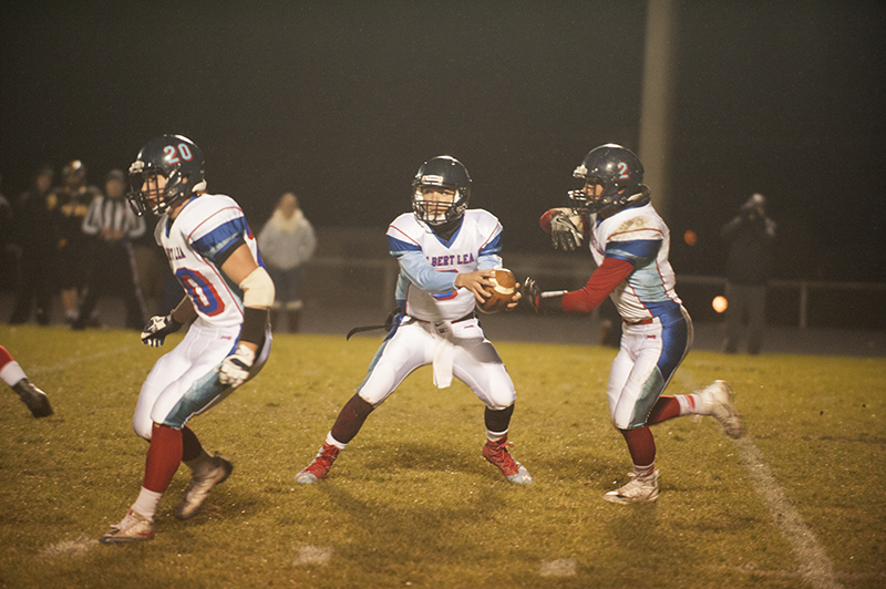 Albert Lea quarterback Sam Chalmers tries to decide whether to keep the ball or hand it off to running back Jessie Hernandez in the first half Tuesday night's game.