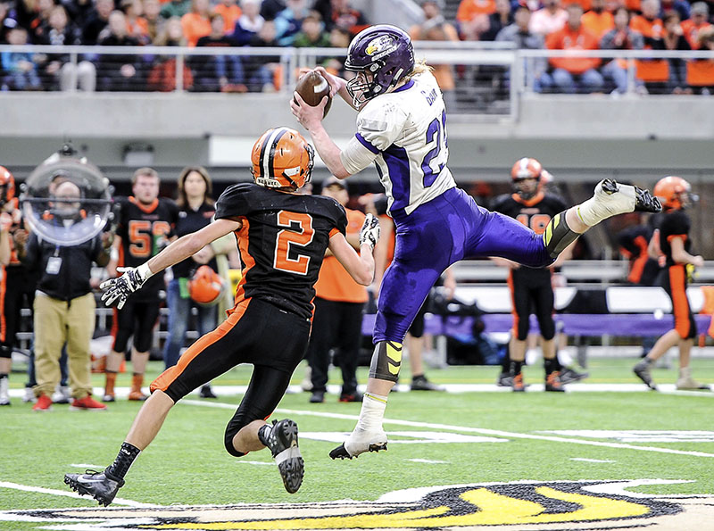 Grand Meadow's Christophor Bain pulls in a pass in the second quarter in front of Cleveland-Immanuel Lutheran's Austin Plonsky in the second quarter of the Minnesota State Nine Man Prep Bowl Friday morning at U.S. Bank Stadium. Eric Johnson/photodesk@austindailyherald.com