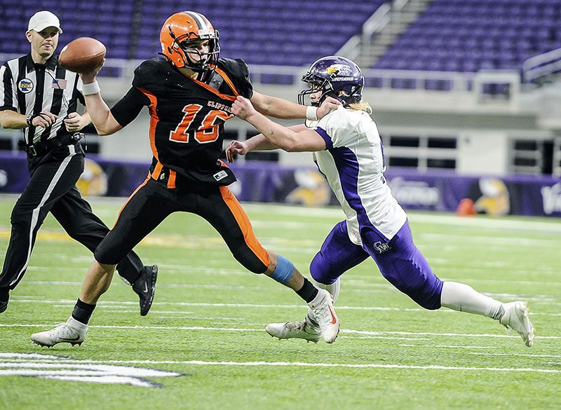 Grand Meadow's Kyle Oehlke gets a hand on Cleveland-Immanuel Lutheran's Carter Kopet during the third quarter of the Minnesota State Nine Man Prep Bowl Friday morning at U.S. Bank Stadium. Eric Johnson/photodesk@austindailyherald.com