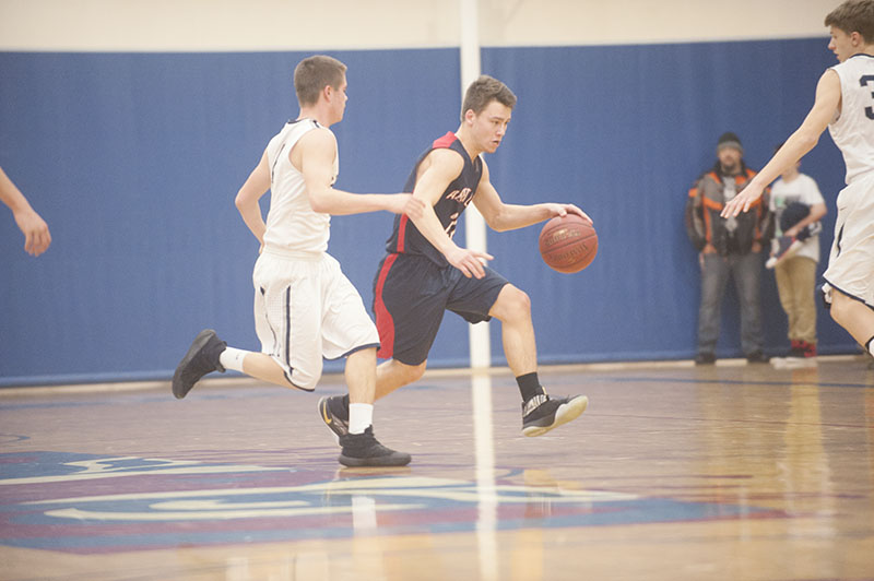 Albert Lea guard Tanner Wichmann tries to beat a Rochester Century defender as he crosses halfcourt in the first half Tuesday night. Wichmann led the Tigers with 19 points.