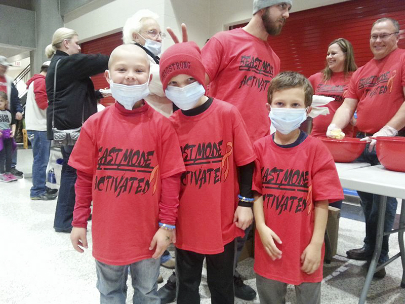 Bebo Getchell, center, makes a surprise appearance at a buzz bash in his honor at United South Central. Getchell must wear a mask while out in public as his immune system is compromised due to his ongoing battle with leukemia. - Provided