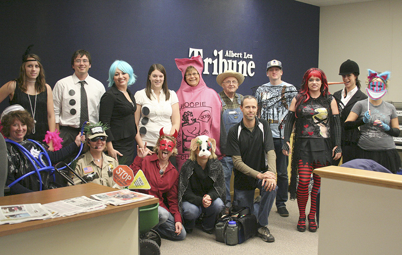Albert Lea Tribune employees pose for a photo on a prior Halloween. Shannon is pictured under the Albert Lea Tribune sign wearing overalls. - Tribune file photo