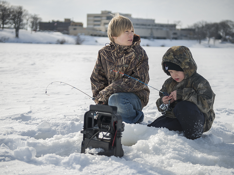 Cousins Fred Tenneson and Marcus Hamberg wait for some bites while ice fishing on Fountain Lake. - Colleen Harrison/Albert Lea Tribune