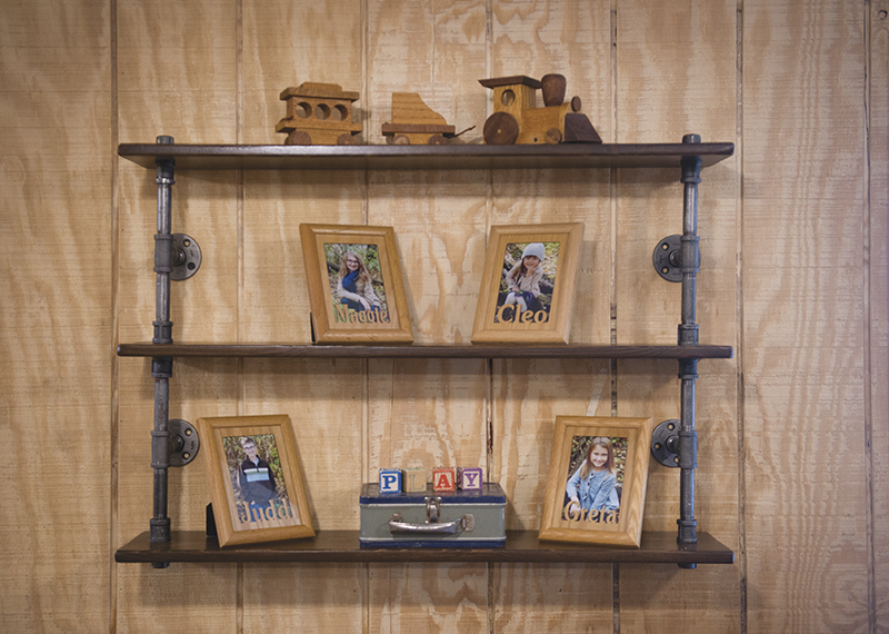 Matt Moller used to be a plumber. Now that he has started his business, Homestead Design, one of the pieces he makes is shelving made out of pipes and wood. - Colleen Harrison/Albert Lea Tribune