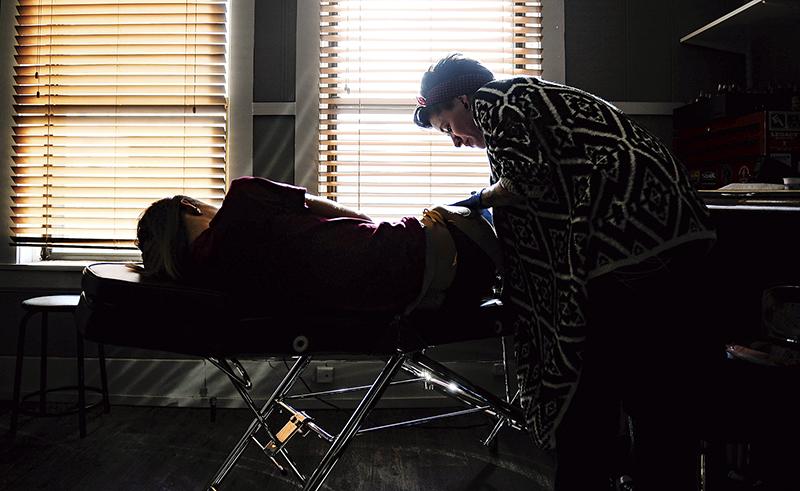 Andrea Nolan watches as Misty Chastain tattoos sunflowers on her leg at Corpus Opus Tattoo. - Eric Johnson/Albert Lea Tribune