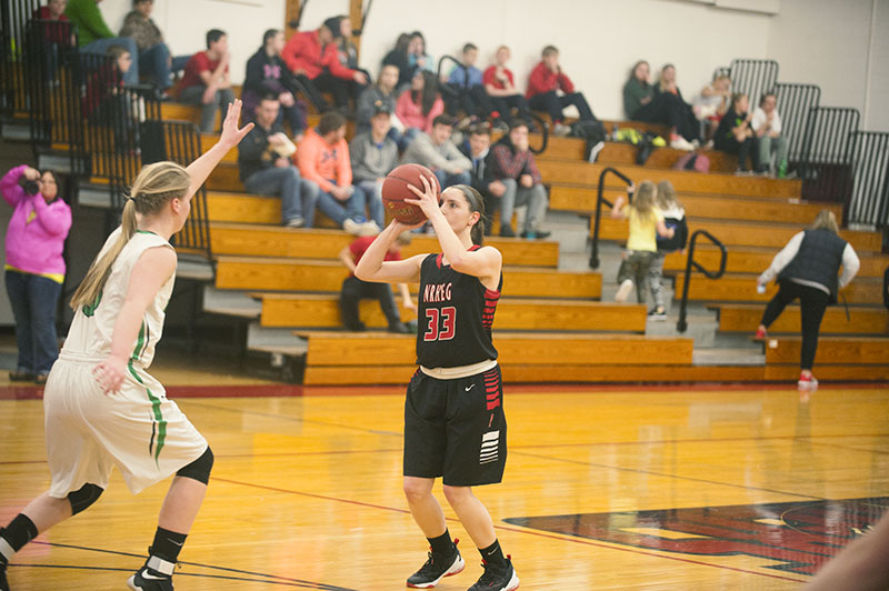 NRHEG forward Kelly Harden takes a shot over Waterville-Elysian-Morristown's Maddy Meskan in the first half Tuesday night.