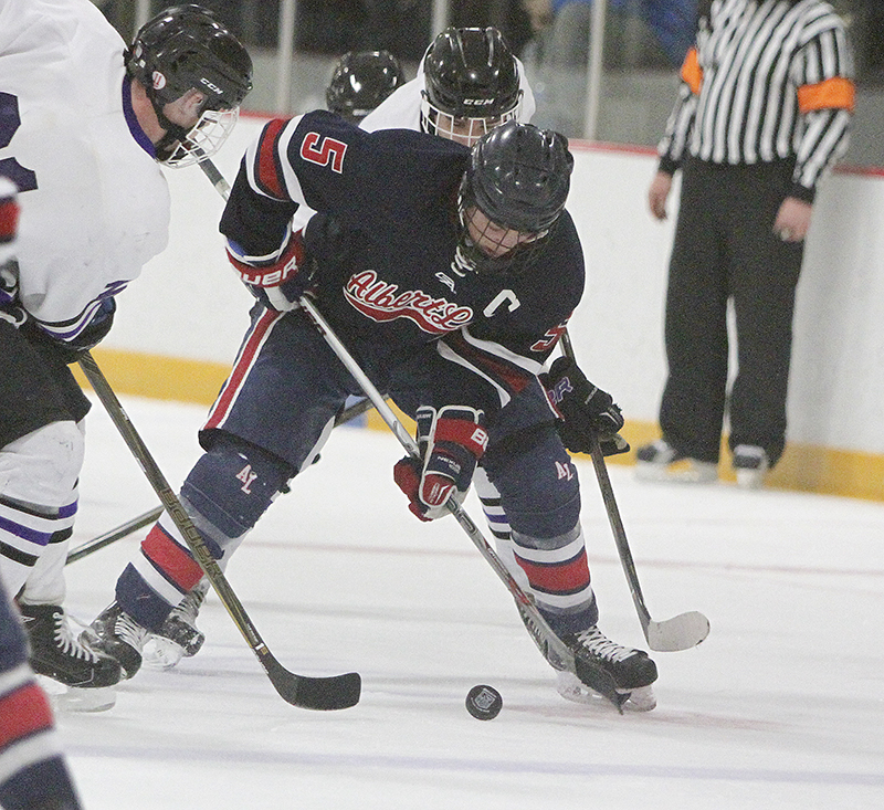 Albert Lea's Sam Chalmers tries to maintain possession of the puck against a pair of Red Wing defenders during Thursday's Section 1A quarterfinal game at Prairie Island Arena.